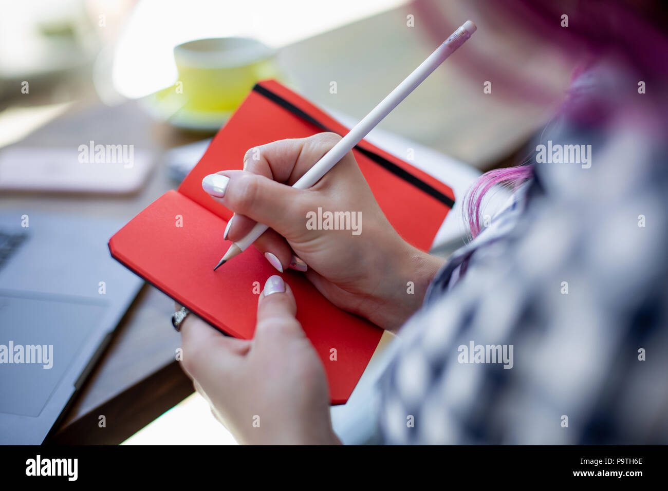 Positive female student with pink hair writing down funny story in notebook sitting in coffee shop with cup of cappuccino and laptop. Smiling female n - Stock Image