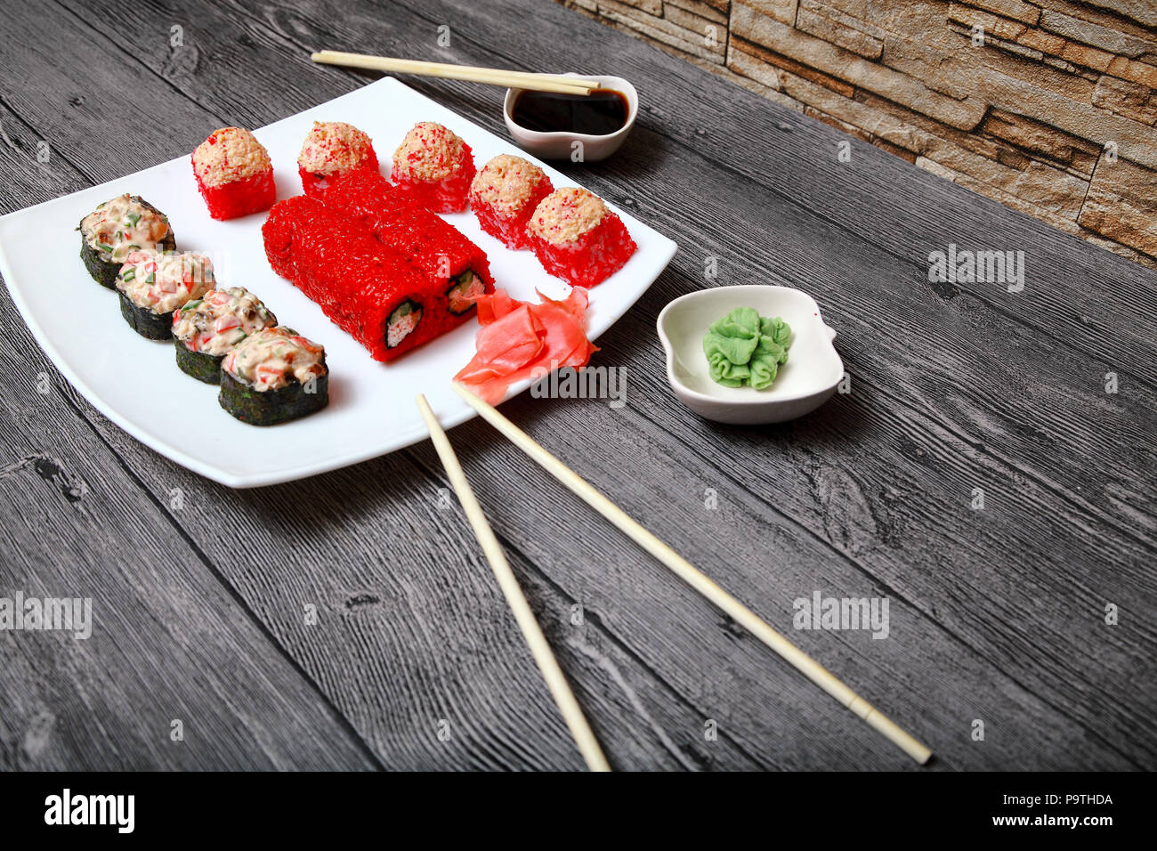Japanese cuisine. On the table of the restaurant are beautifully laid out a set of rolls, sauce, ginger and wasabi. Stock Photo