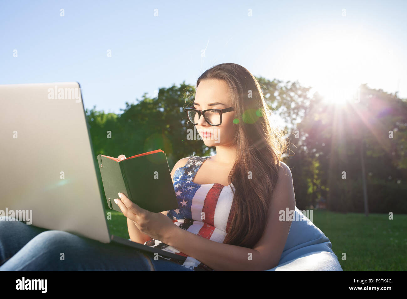 Pretty young woman sitting on bean bag use laptop while resting on grass in park on the sun. Success small business, modern lifestyle, information tec - Stock Image