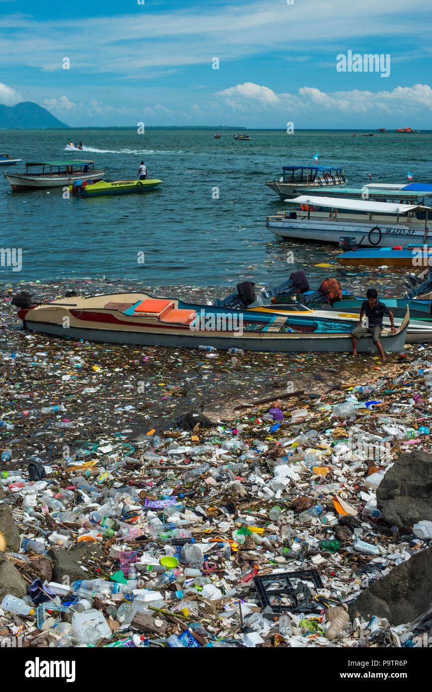 Plastic pollution floating next to small boats at the waterfront in Semporna town in Sabah, (Malaysian Borneo), Malaysia. - Stock Image