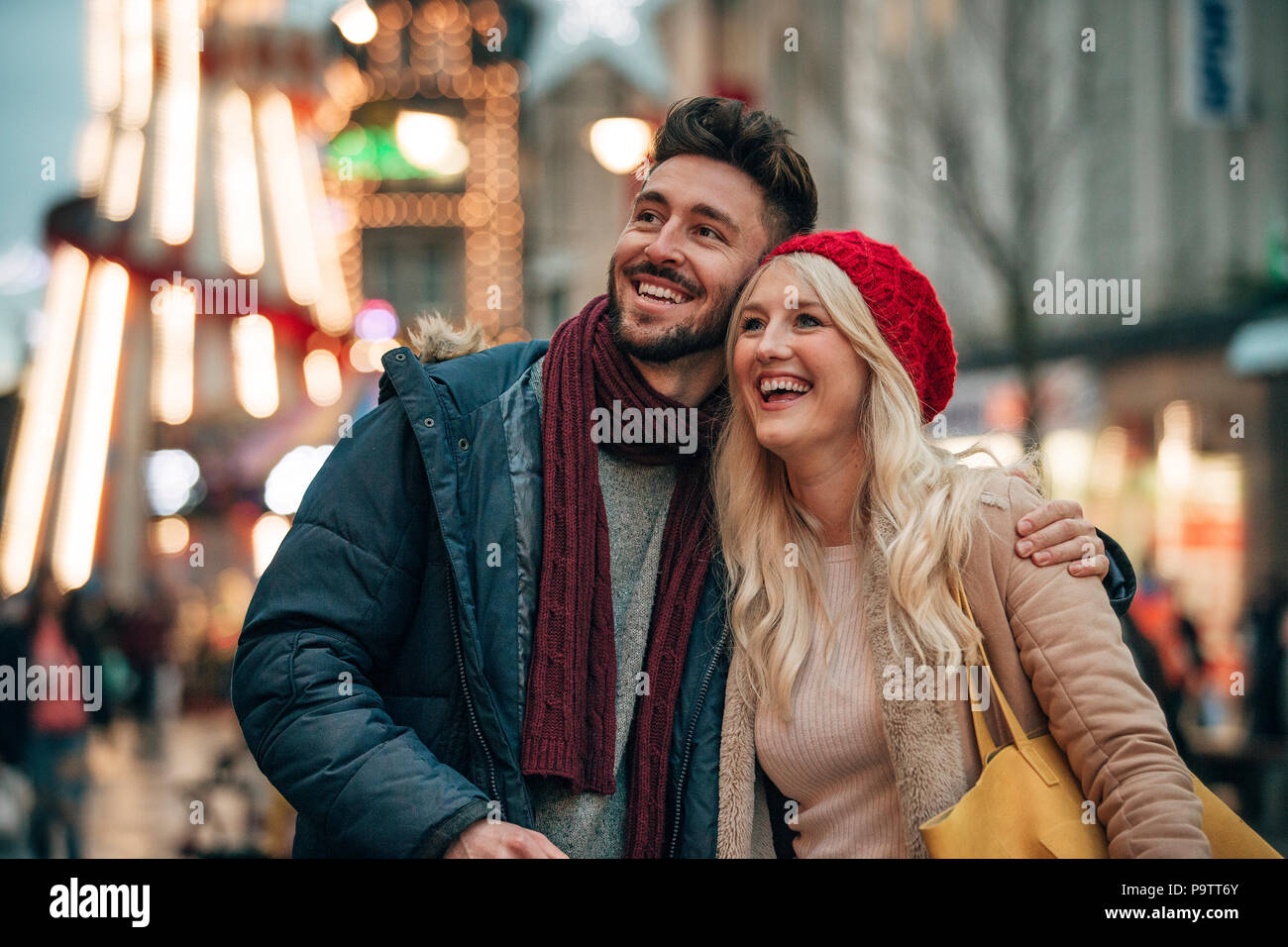Front view of a man with his arm around his girlfriend outside. The couple are outside on a city street . There is a fair groung ride in the backgroun - Stock Image