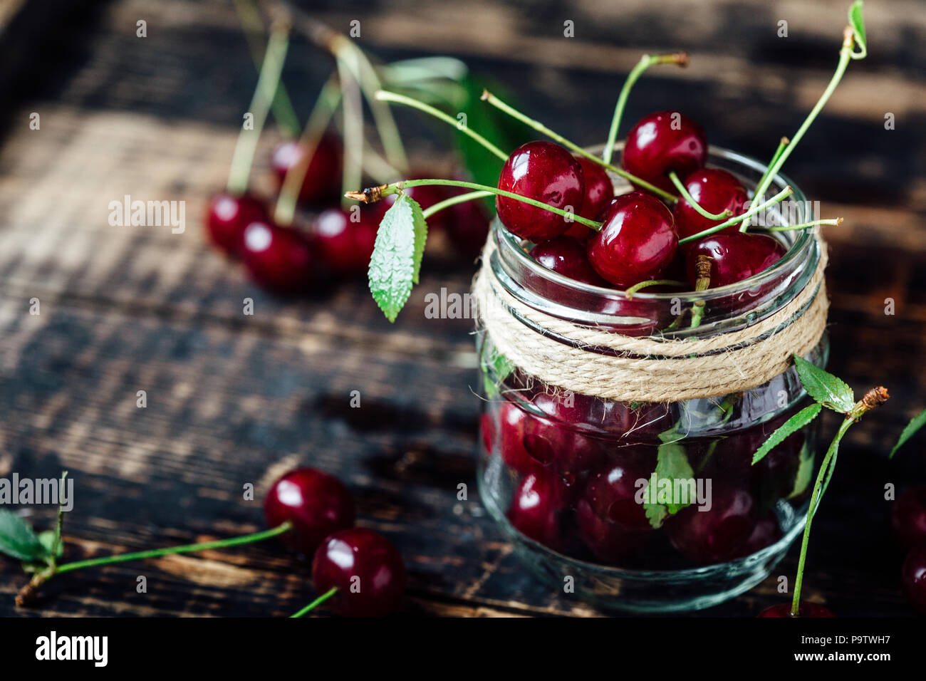 Fresh ripe cherries on a wooden table. Wooden background - Stock Image