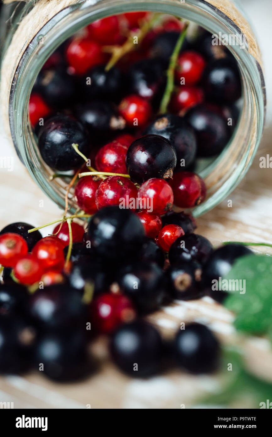 Fresh ripe red and black currants on the background of a wooden table. Wooden background - Stock Image