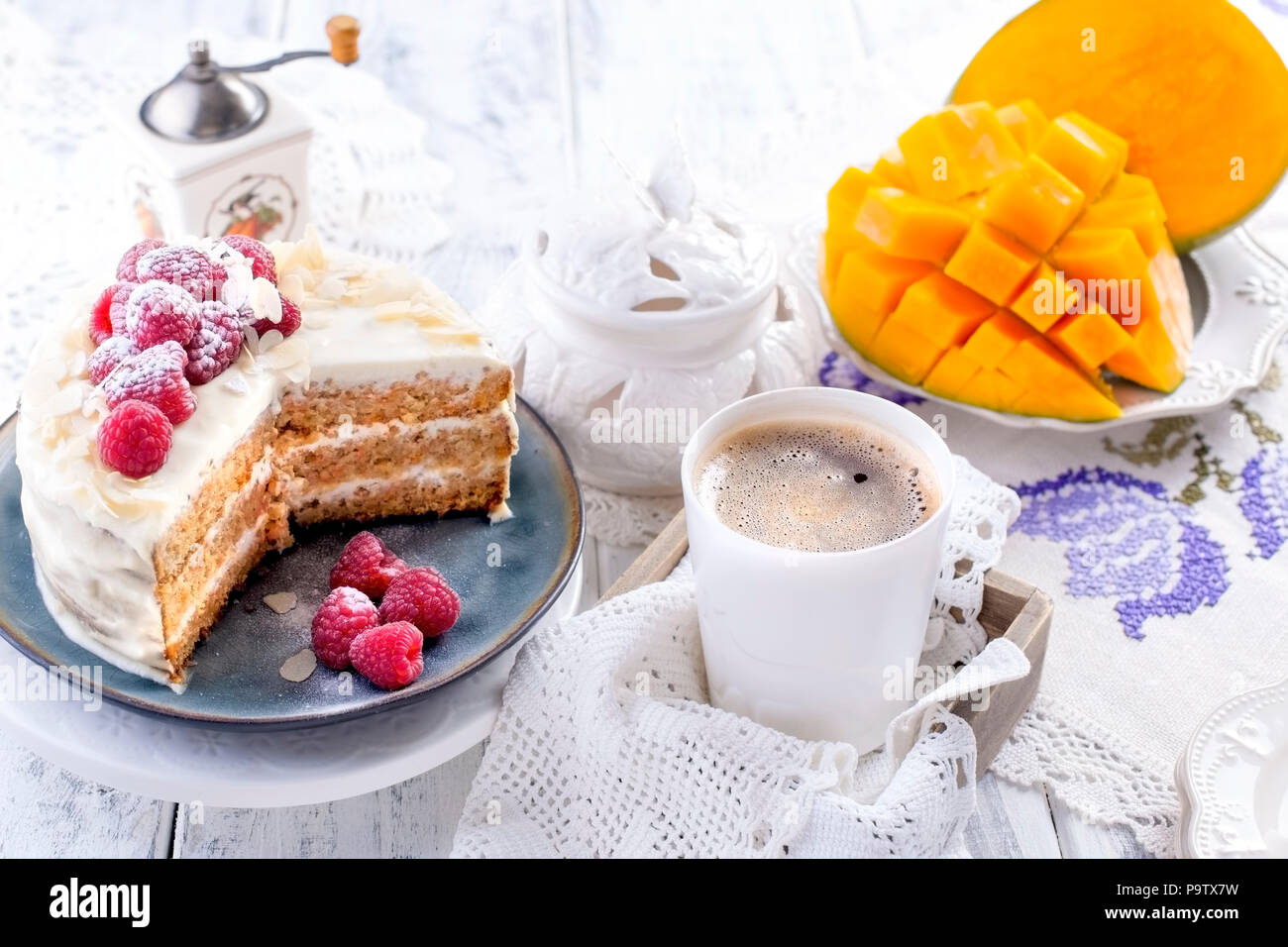 Cut the cake with white cream, for breakfast. A mango fruit. White background, tablecloth with lace, a cup of fragrant black coffee and free space for text or advertising. - Stock Image