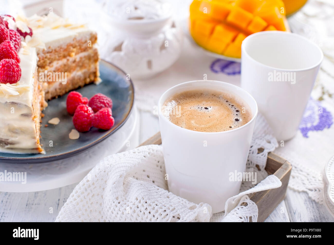 Cut the cake with white cream, for breakfast. A mango fruit. White background, tablecloth with lace, a cup of coffee and free space for text or advertising. - Stock Image