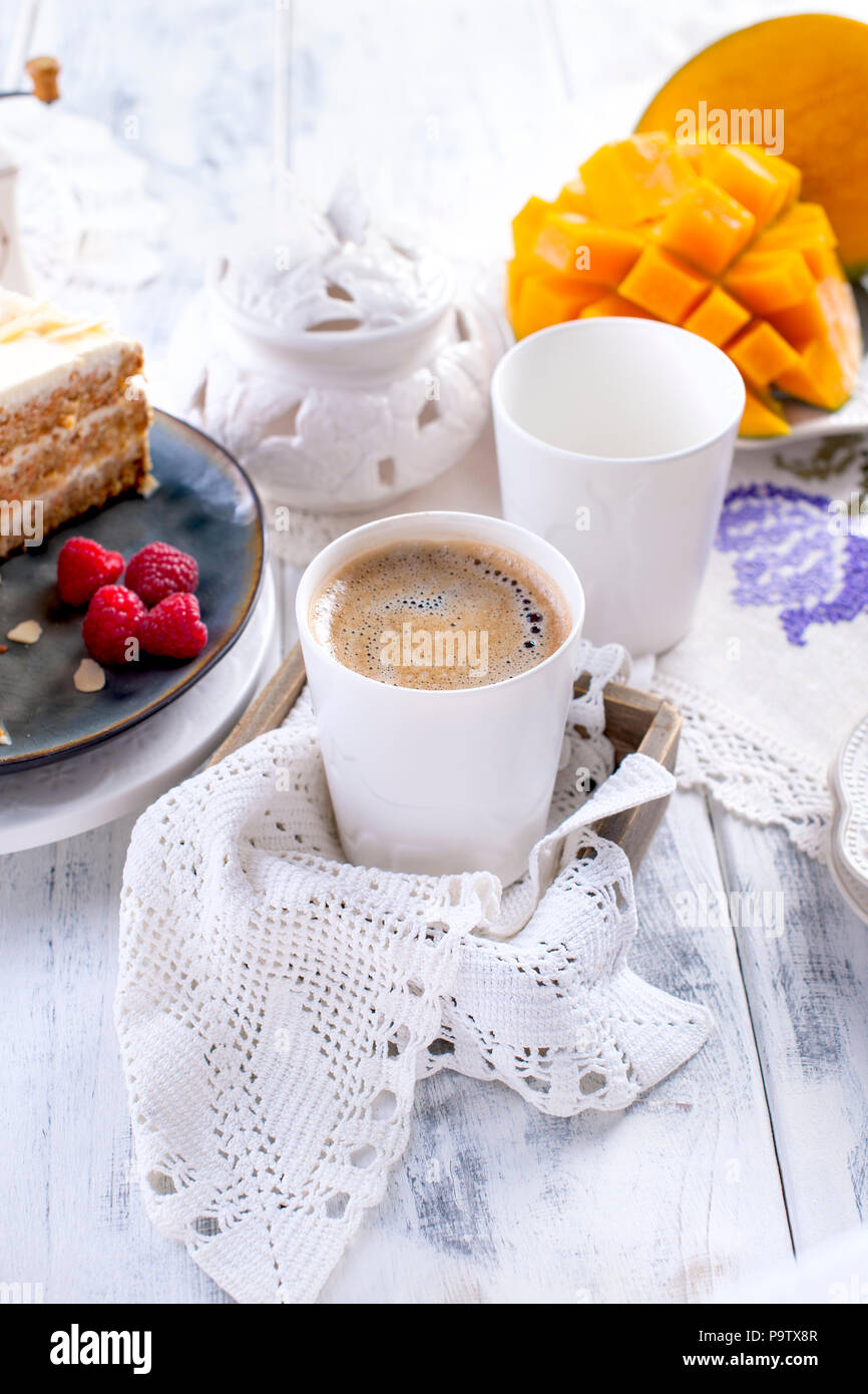 Cut the cake with white cream, for breakfast. A mango fruit. White background, tablecloth with lace, a cup of coffee and free space for text or advertising - Stock Image