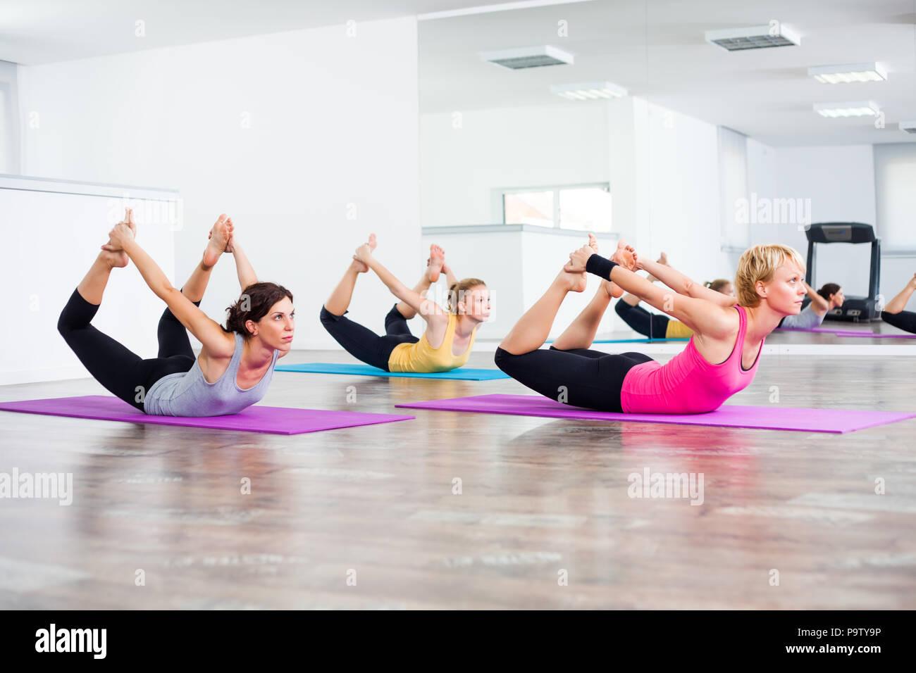 Three girls practicing yoga, Dhanurasana / Bow pose Stock Photo