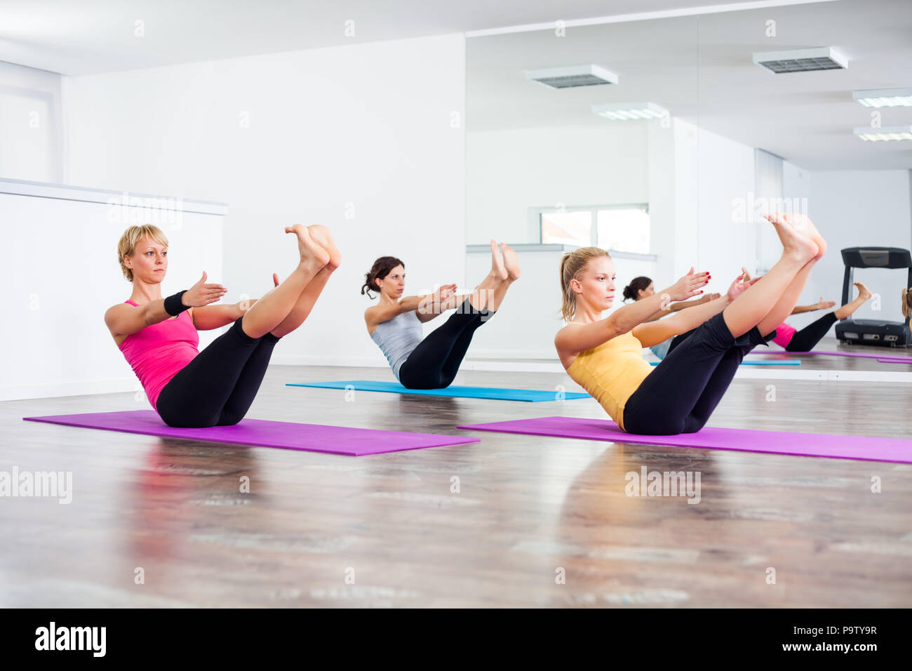 Three girls practicing yoga, Navasana / Boat Pose - Stock Image