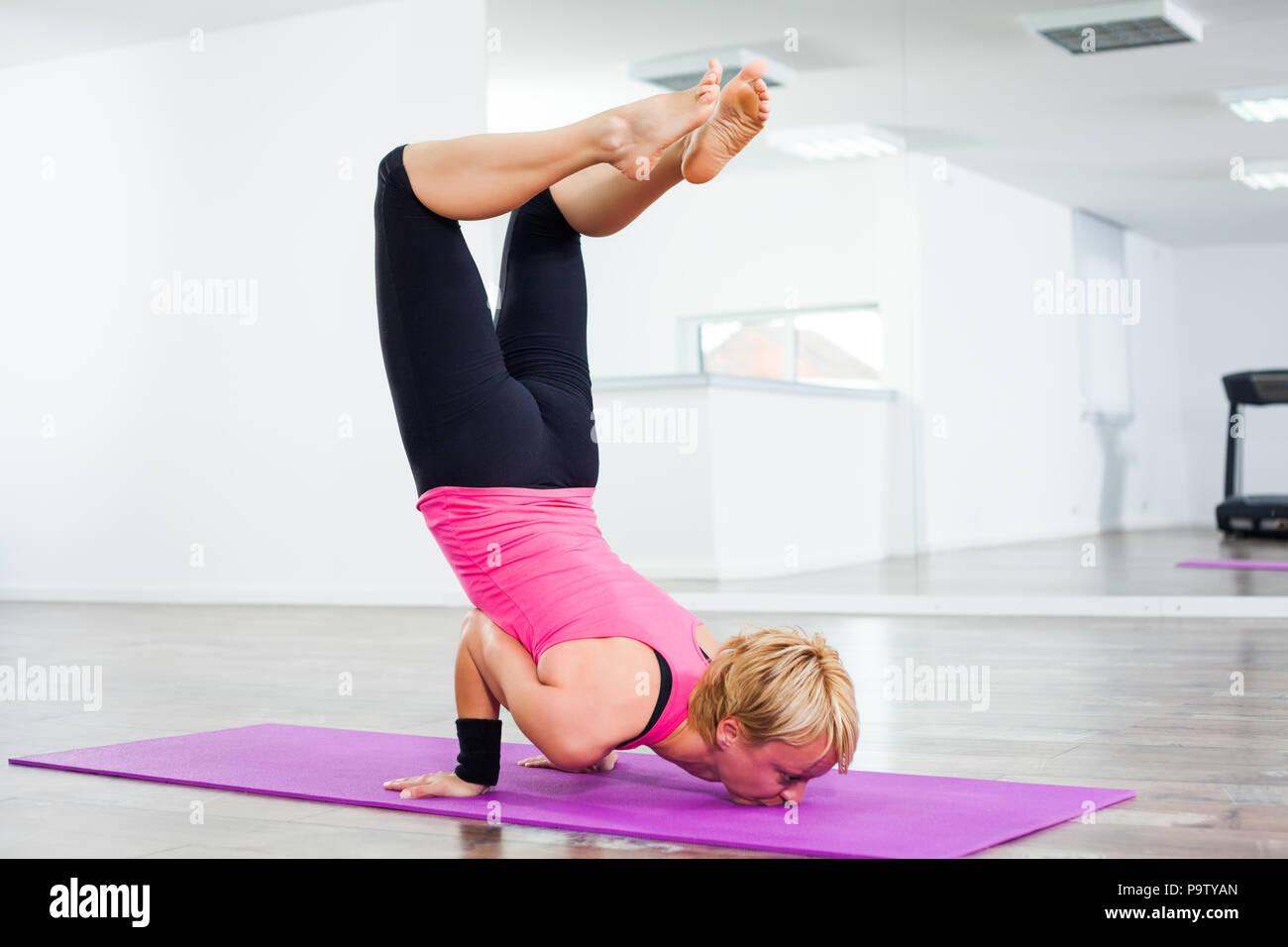 1aed87c9ebfe4 Young woman practicing yoga, Vrschikasana / Scorpion pose Stock ...
