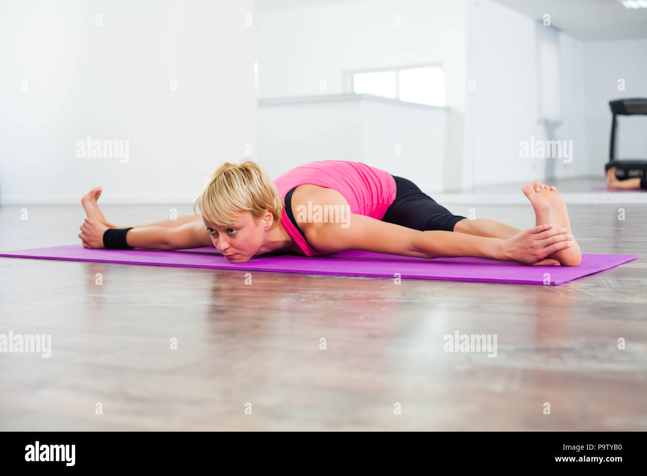 Young woman practicing yoga, Upavistha Konasana / Seated Angle Pose - Stock Image