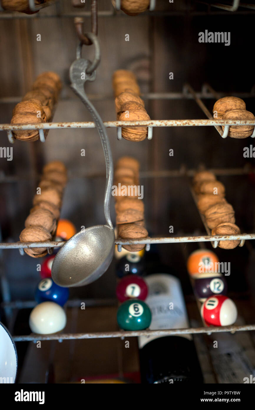 detail of unusual collection of objects displayed in old rack, including walnuts, pool balls, an old ladle and a bottle of wine - Stock Image