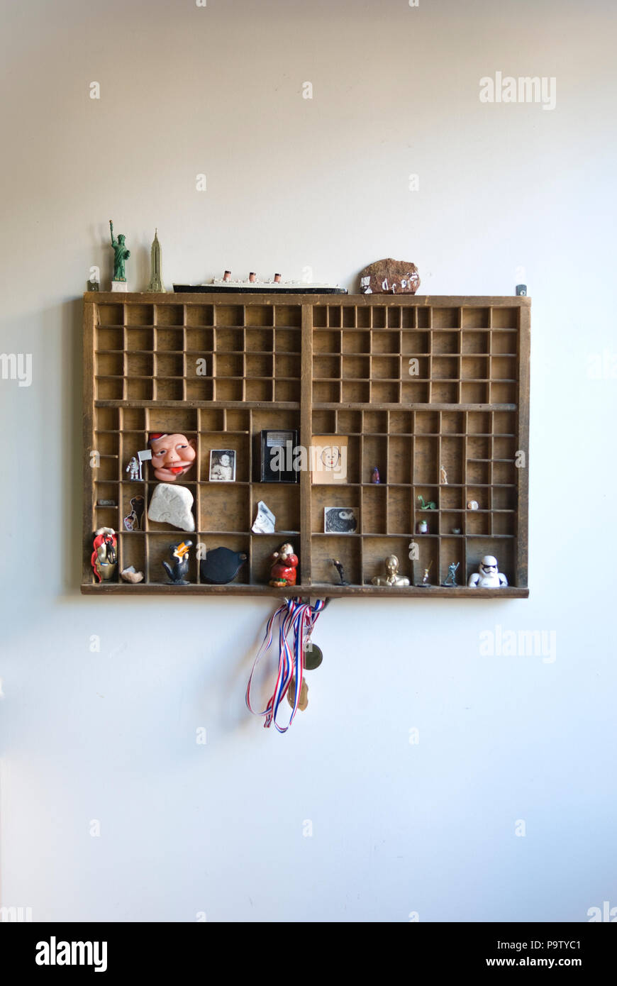 interior shot of old printers drawer on wall of kid's bedroom filled with an eclectic range of objects, including old toy liner and figurines - Stock Image