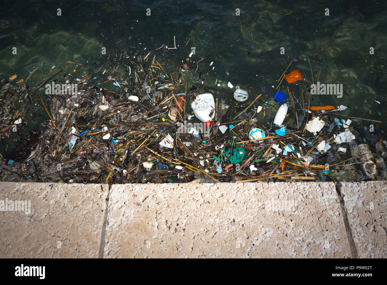 a depressing landscape view from a  seawall in Croatia looking down at the terrible pollution of the adriatic sea with floating plastic in many forms - Stock Image