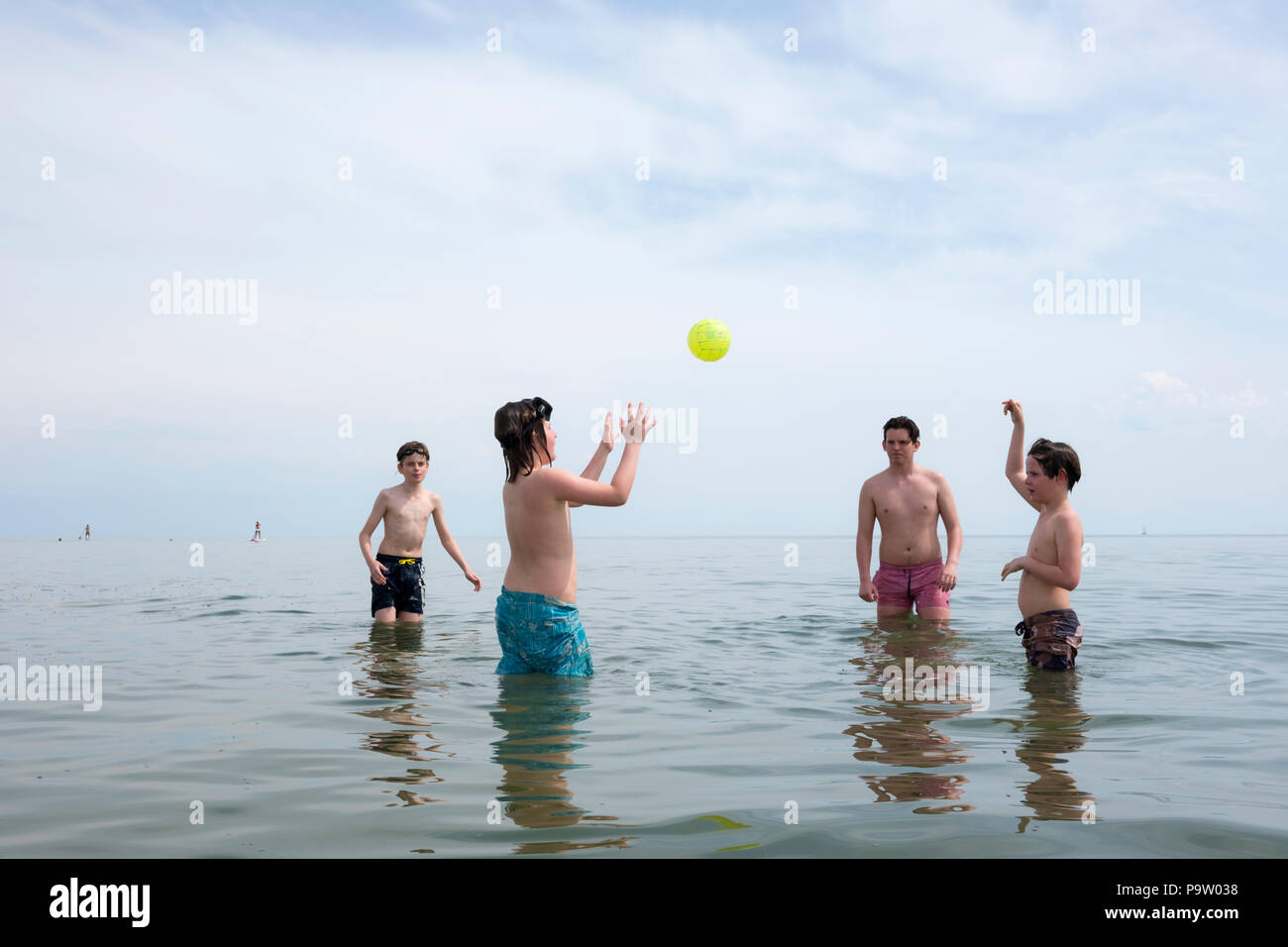 landscape view of four boys in a circle, standing up to their knees in a calm mediterranean sea, playing catch with a yellow ball. - Stock Image