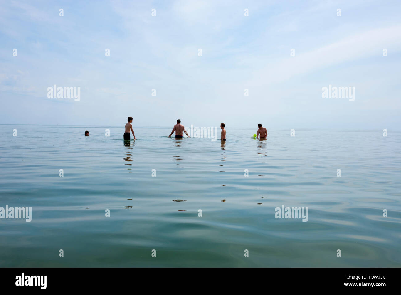 landscape view of four boys and a male adult standing up to their waists in a calm mediterranean sea, laughing during a game playing with yellow ball - Stock Image