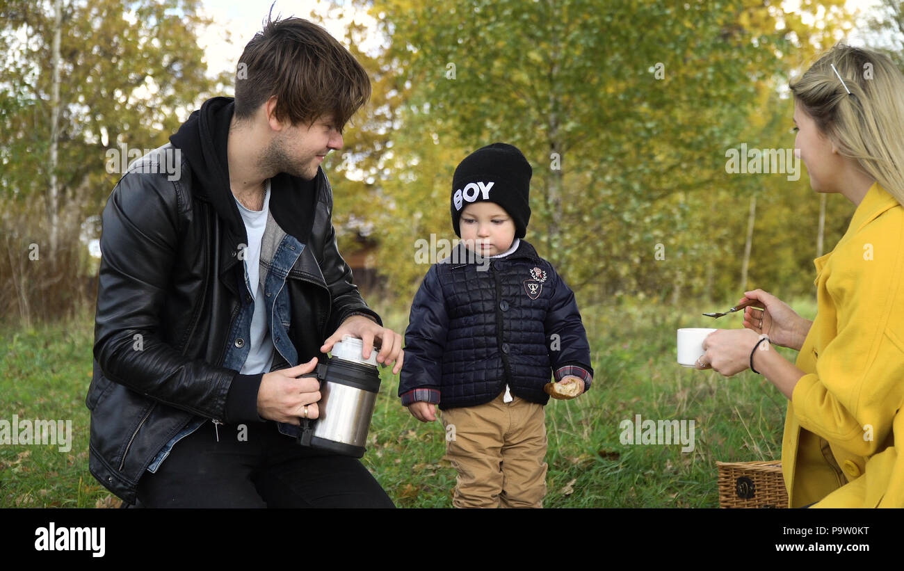 Young family with son at a picnic in the park on a sunny day. Family having picnic outdoors. Young smiling family doing a picnic on an autumns day. Family picnicking together. - Stock Image