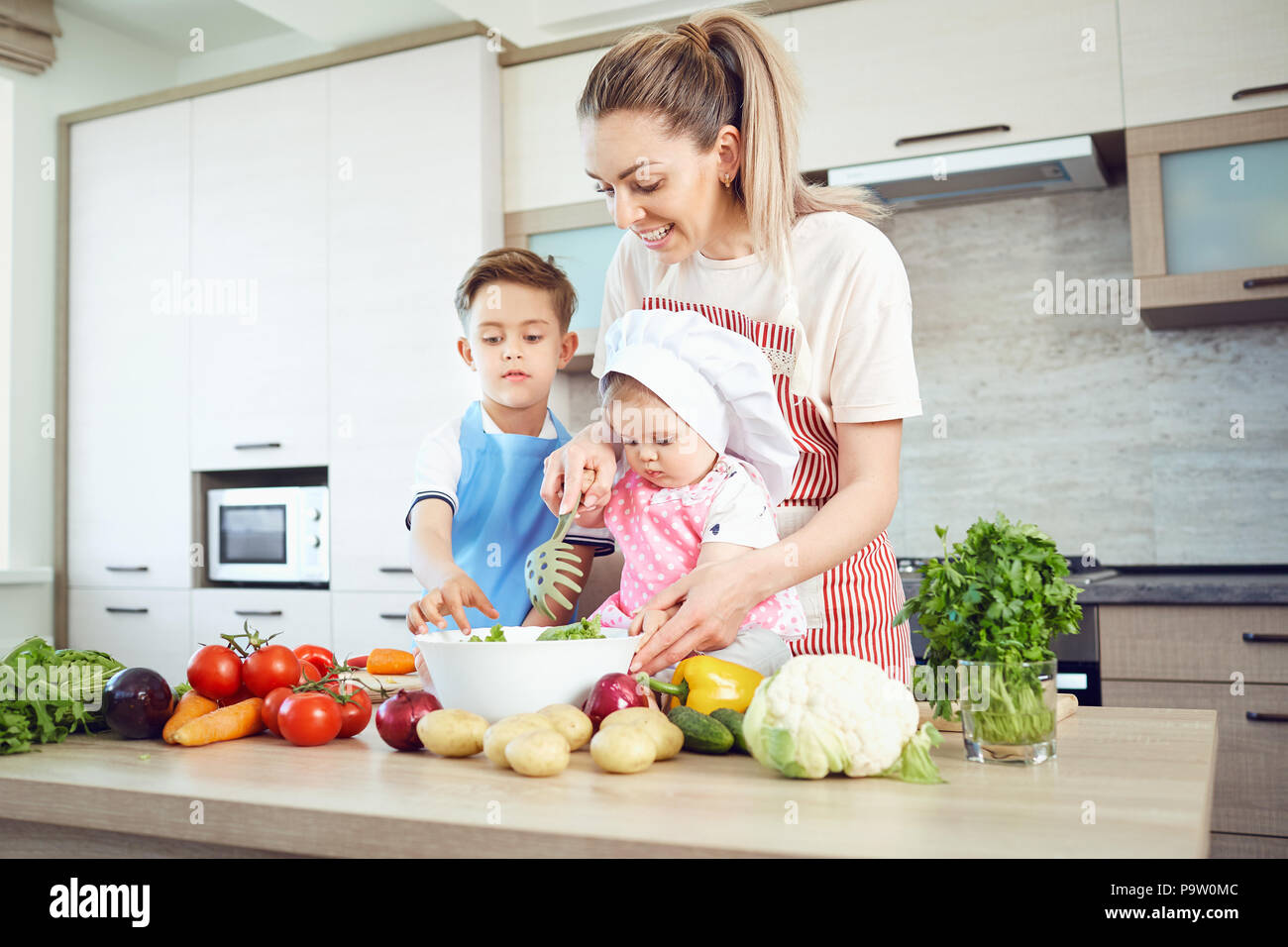 Mother and children are cooking in the kitchen - Stock Image