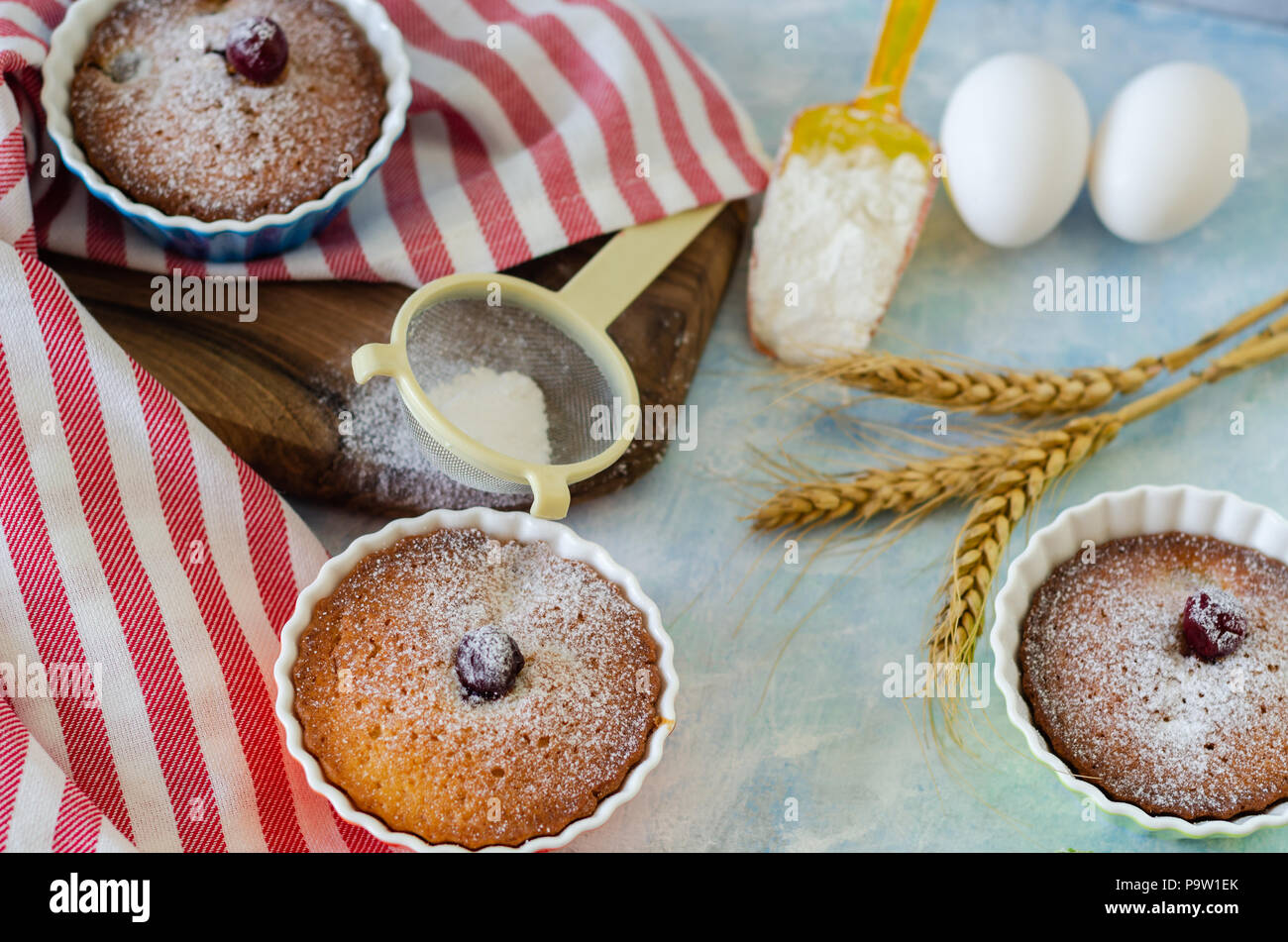 Cakes with cerries on a table in small porcelain cups .There are  eggs, flour, wheat, powdered sugar next to cakes. Stock Photo