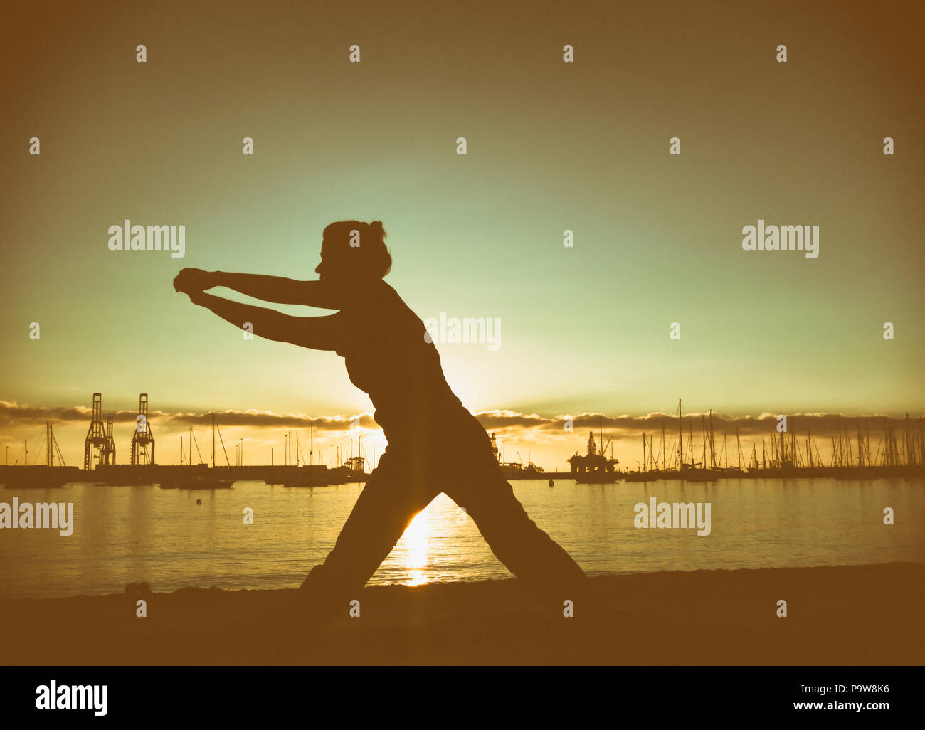 Woman practising Tai Chi and Yoga on city beach - Stock Image