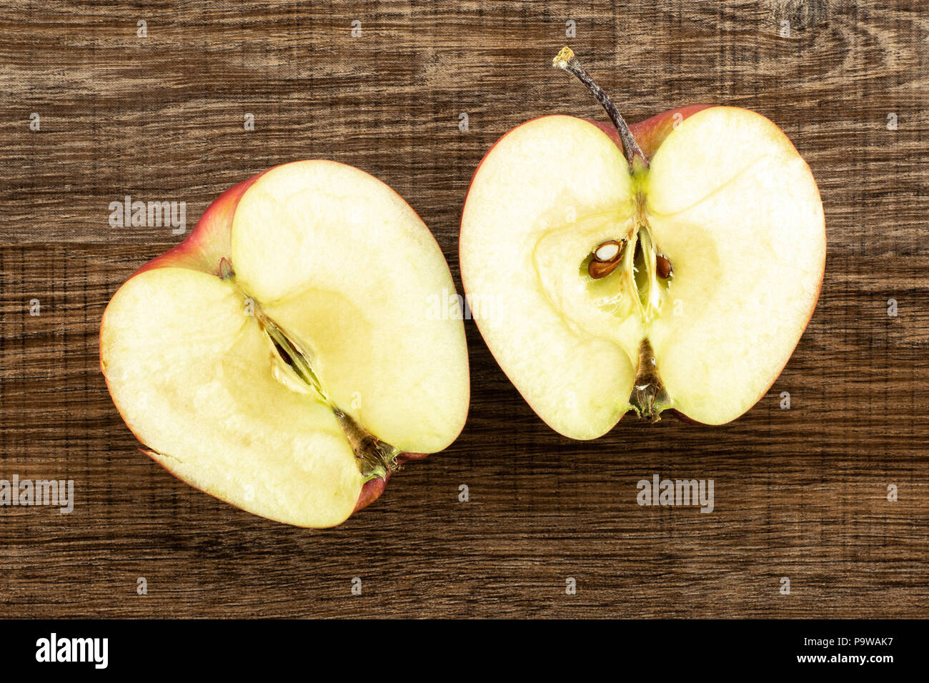 Red delicious apple two section halves flatlay on brown wood background - Stock Image