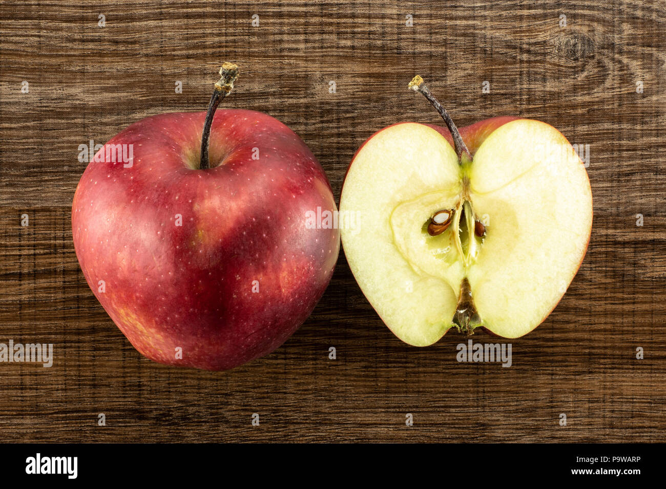 Red delicious one apple and section half flatlay on brown wood background - Stock Image