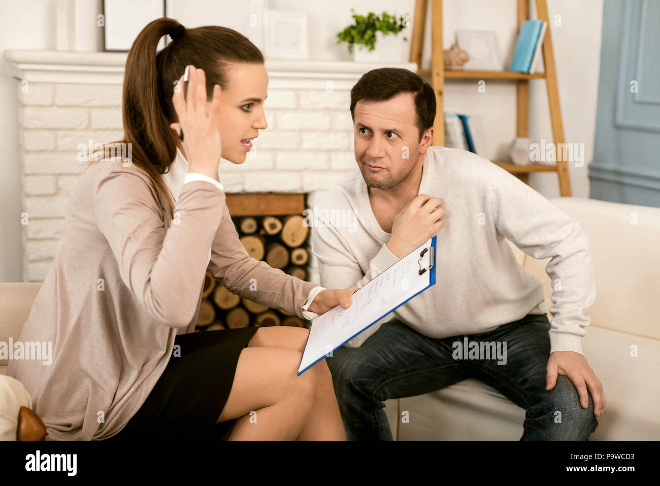 Stressful job. Nice pleasant stressed out woman holding her notes and talking with the patient while working as a psychologist - Stock Image