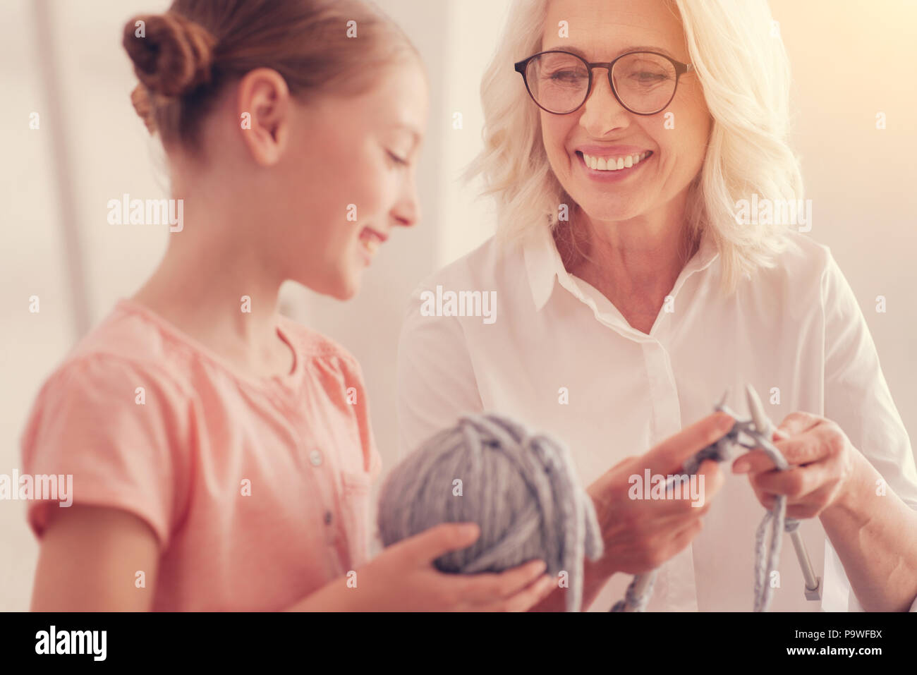 No time for worries. Selective focus on a happy grandmother grinning broadly while having a pleasant conversation with her loving granddaughter during - Stock Image