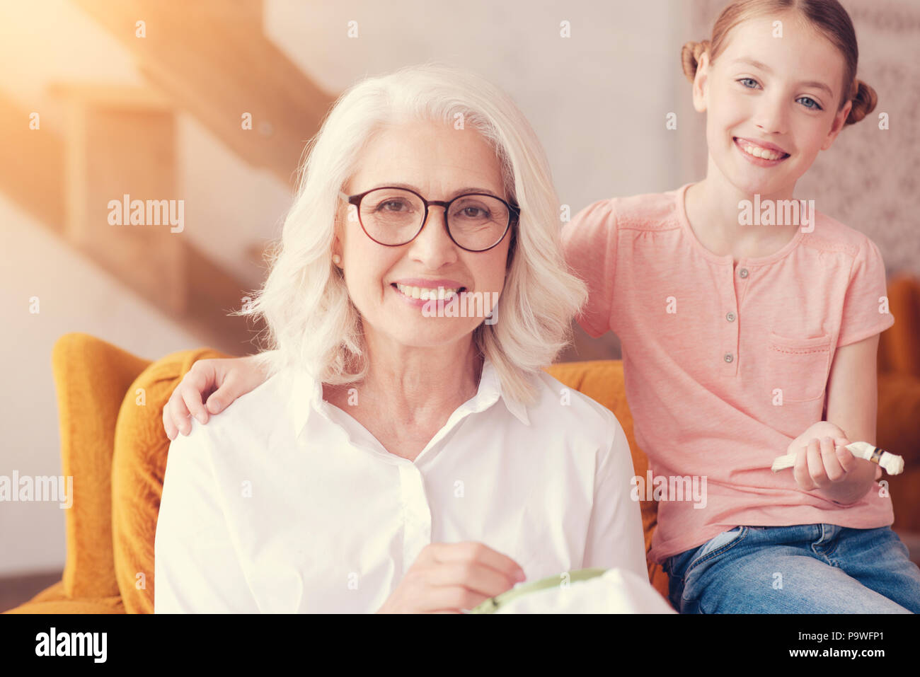 Family ties. Positive minded young lady embracing her beautiful granny in an armchair and both posing for the camera with cheerful smiles on their fac - Stock Image