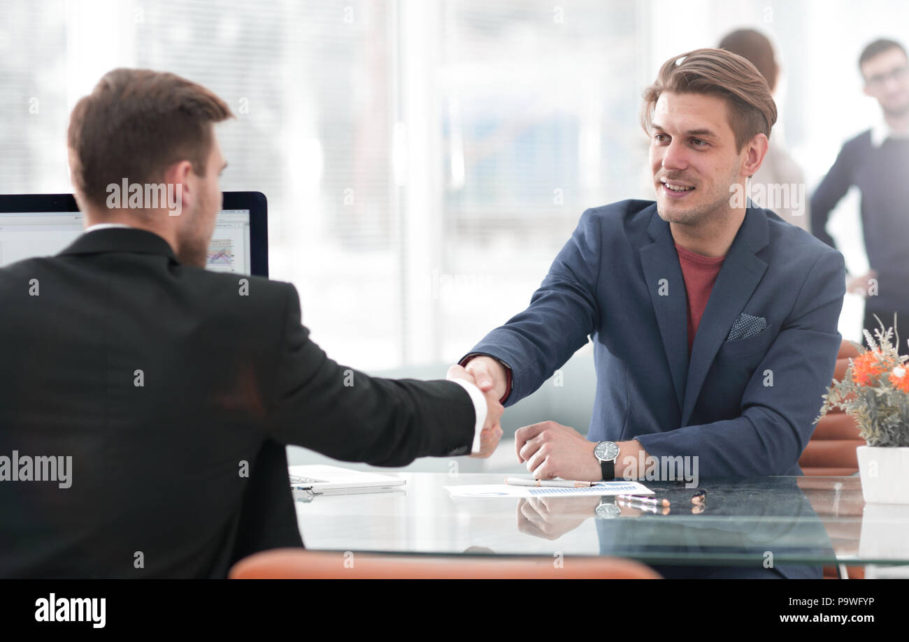 Businessmen shaking hands in conference room in office - Stock Image