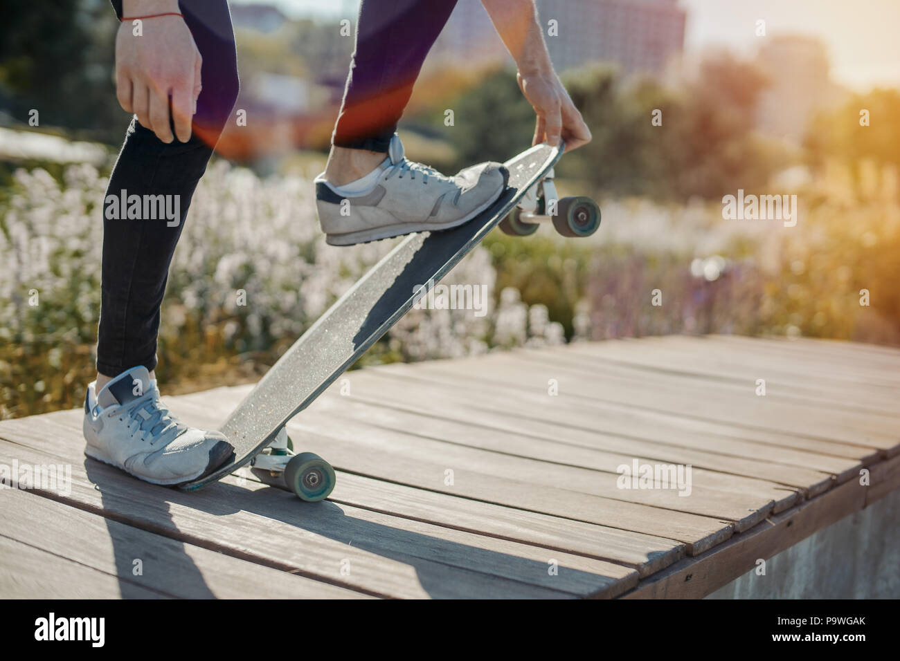 Close up of young attractive man riding longboard in the park. - Stock Image