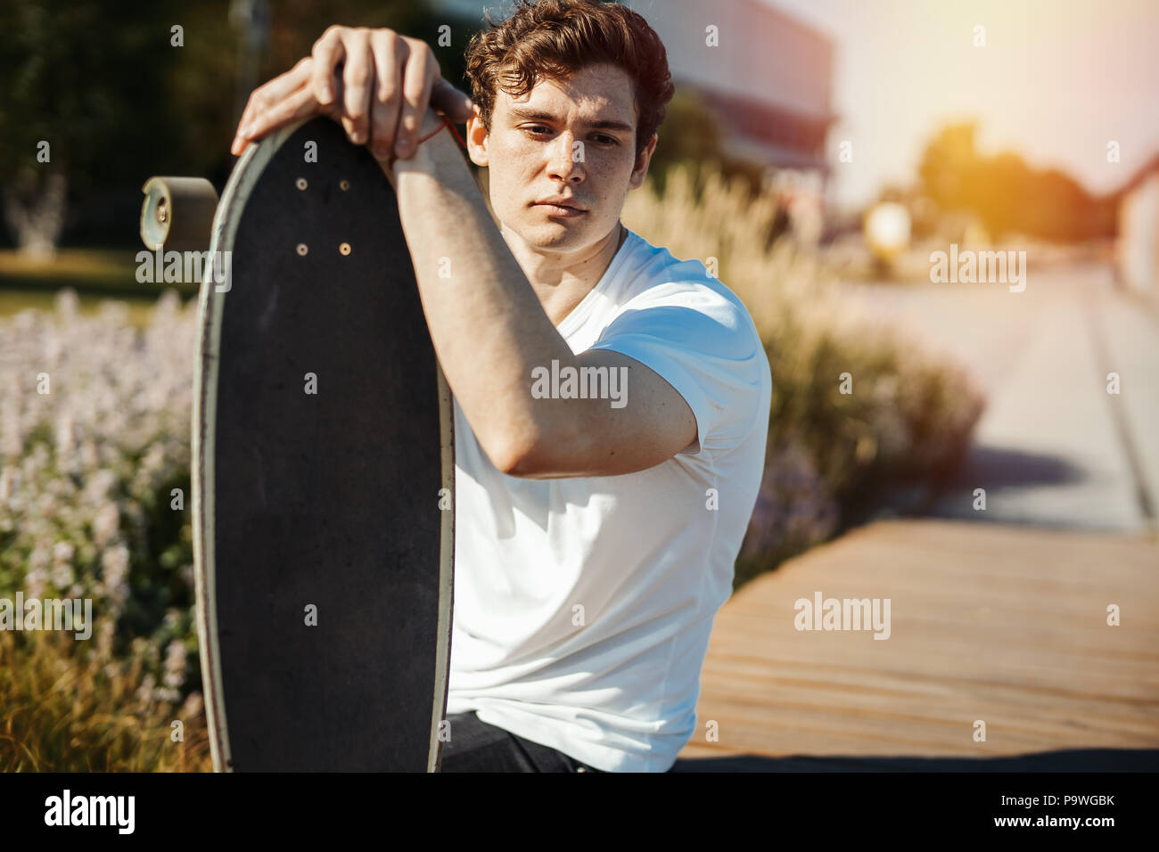Young attractive man sitting on the bench in the park and holding longboard. - Stock Image