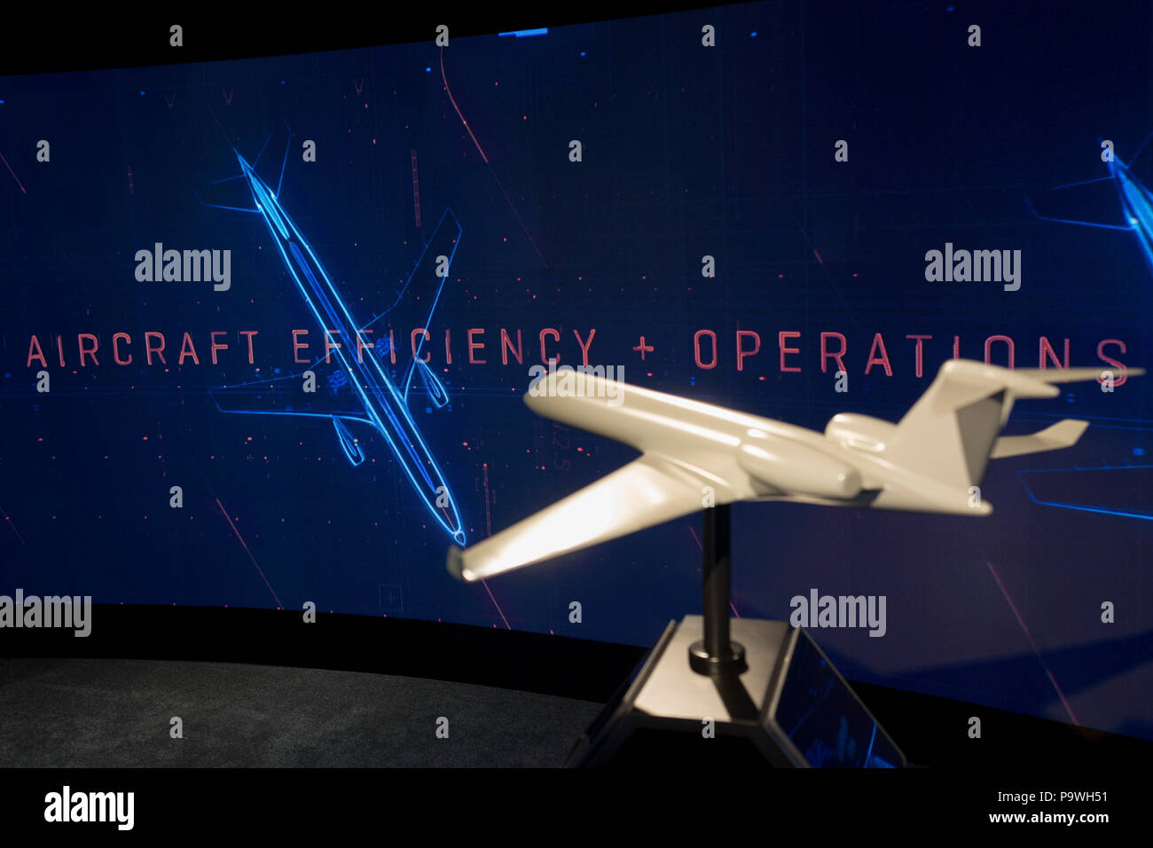 A model of a generic aircraft and the images from a video presentation in the exhibition chalet of United Technologies, at the Farnborough Airshow, on 16th July 2018, in Farnborough, England. United Technologies are the parent company to  Otis,, UTC Climate, Controls & Security, Pratt & Whitney and UTC. - Stock Image