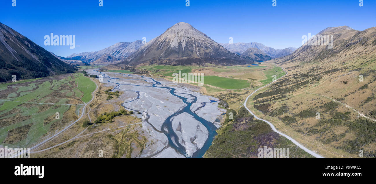 Drone shot, meandering river in sweeping riverbed with mountains, Harper River, Mount Ida, Canterbury region, South Island - Stock Image