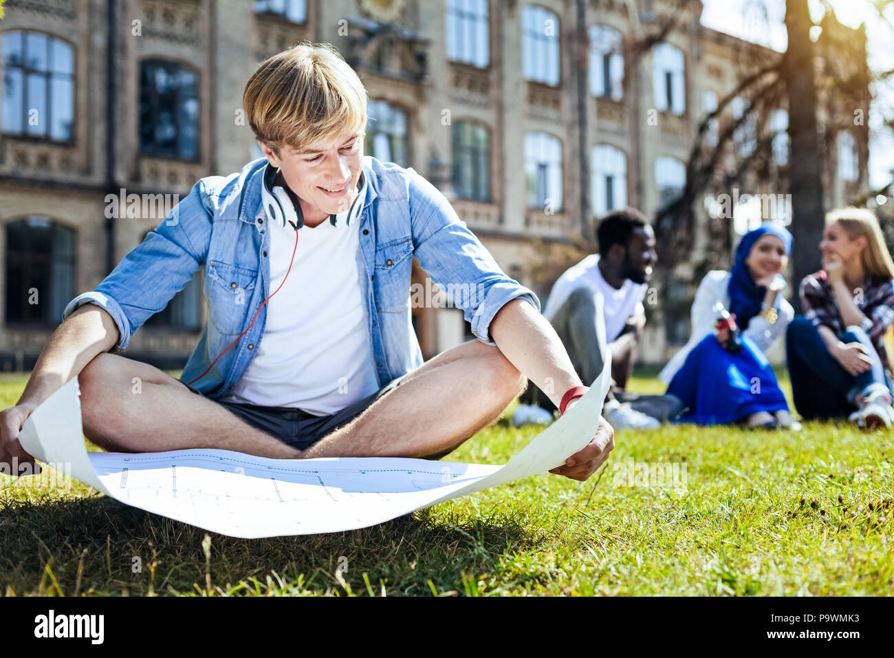 Joyful guy looking at his project outdoors - Stock Image