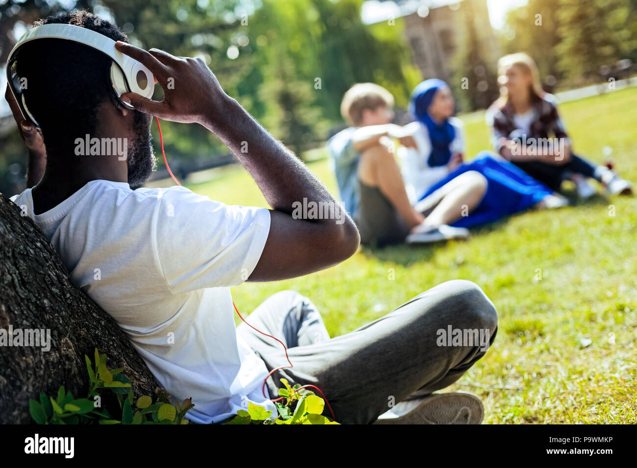Relaxed young man listening to music outdoors - Stock Image