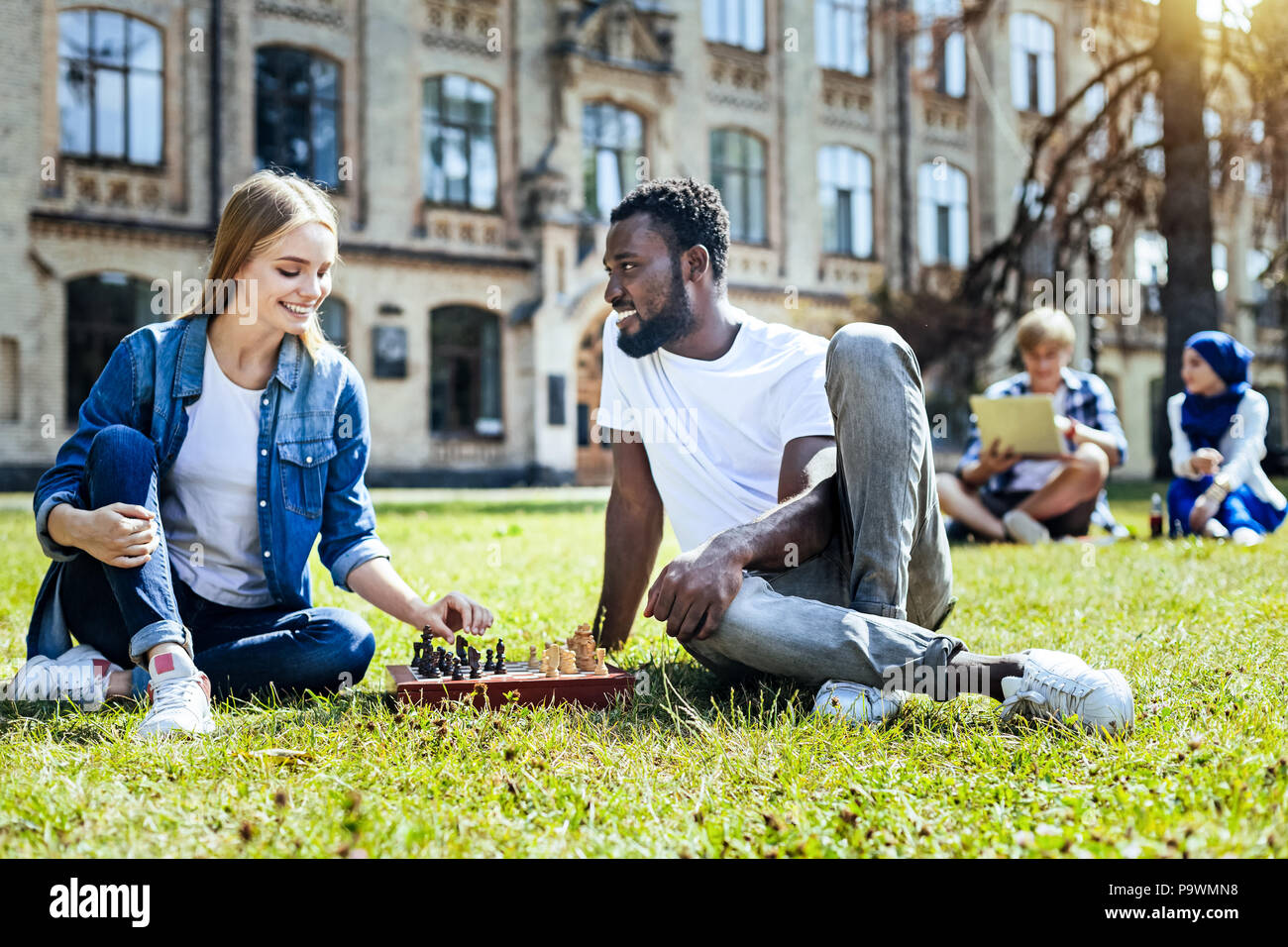 Joyful young people playing chess outdoors - Stock Image
