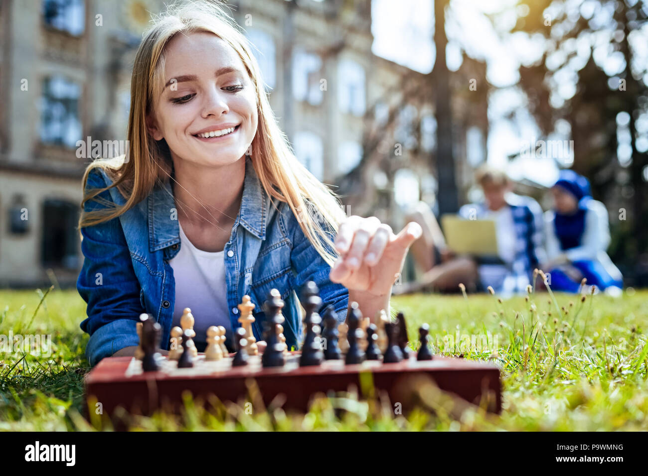 Smart young lady smiling while playing chess - Stock Image