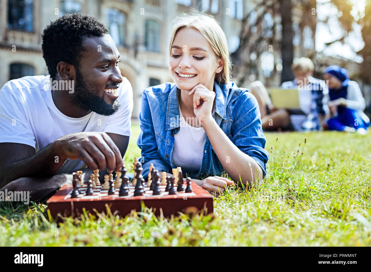 Relaxed friends enjoying chess game together - Stock Image