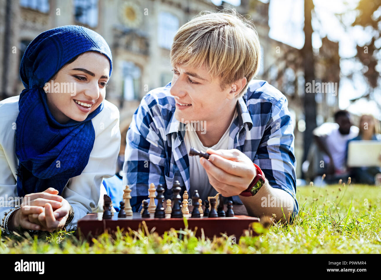 Friendly guy teaching girl playing chess - Stock Image