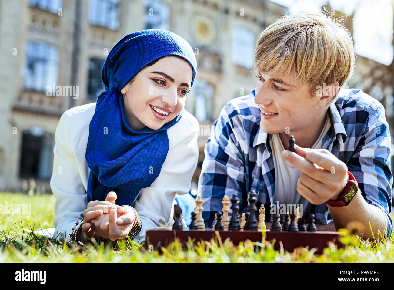 Beaming young people enjoying chess game outdoors - Stock Image