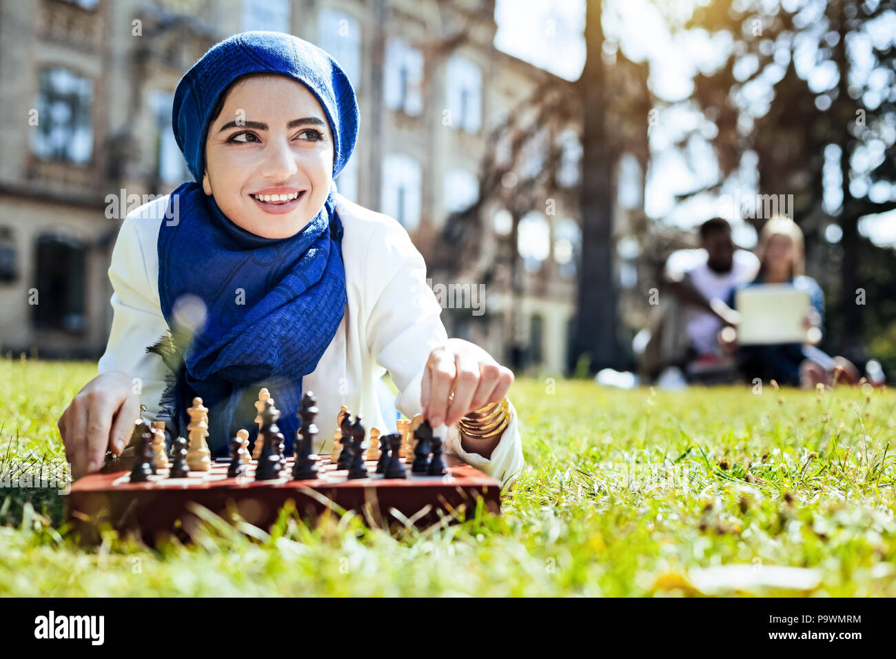 Beautiful girl dreaming while playing chess - Stock Image