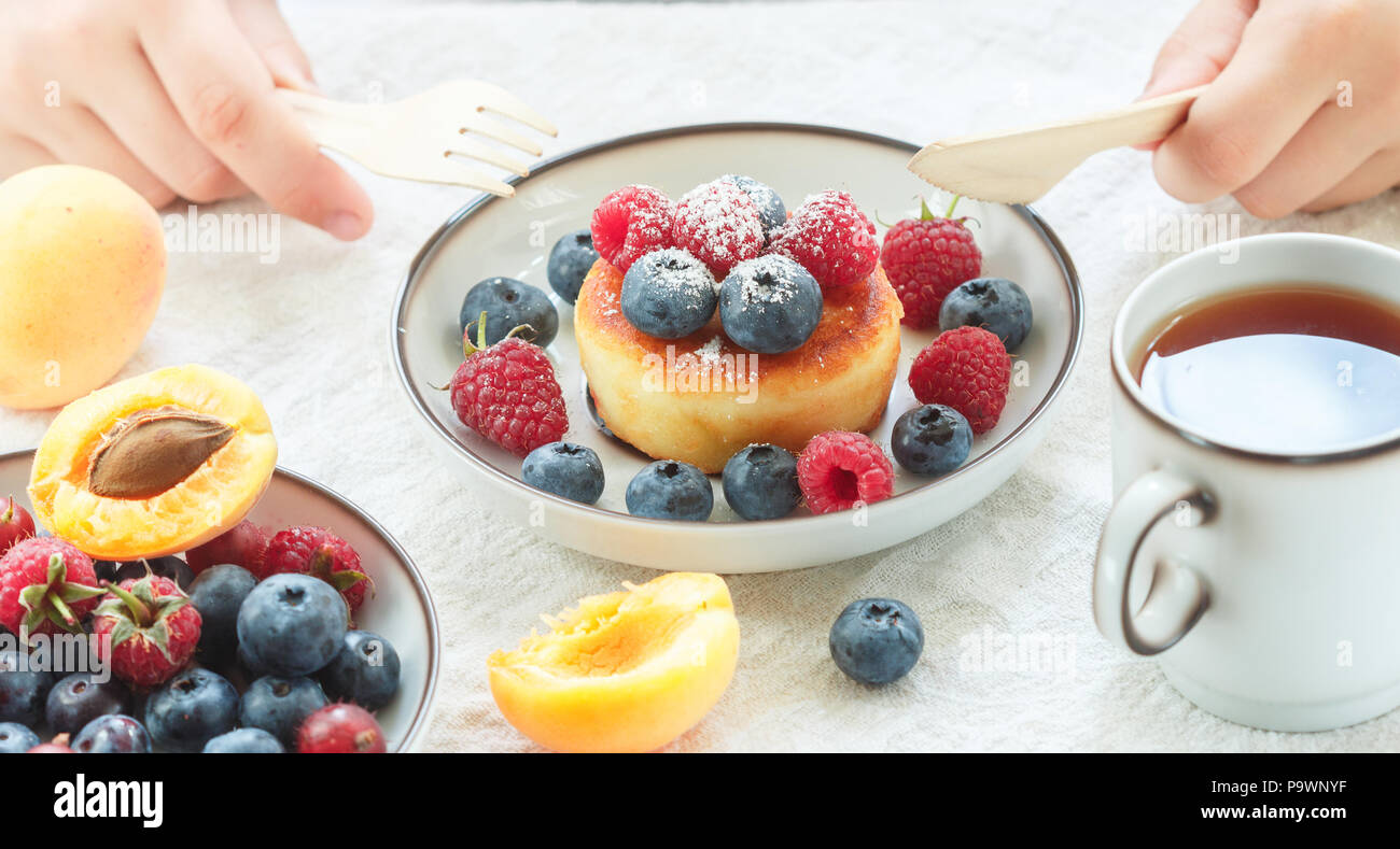 Cottage cheese pancakes, syrniki, curd fritters with fresh berries (raspberry, blueberry, apricot) and powdered sugar in a white plate.  Tasty and hea Stock Photo