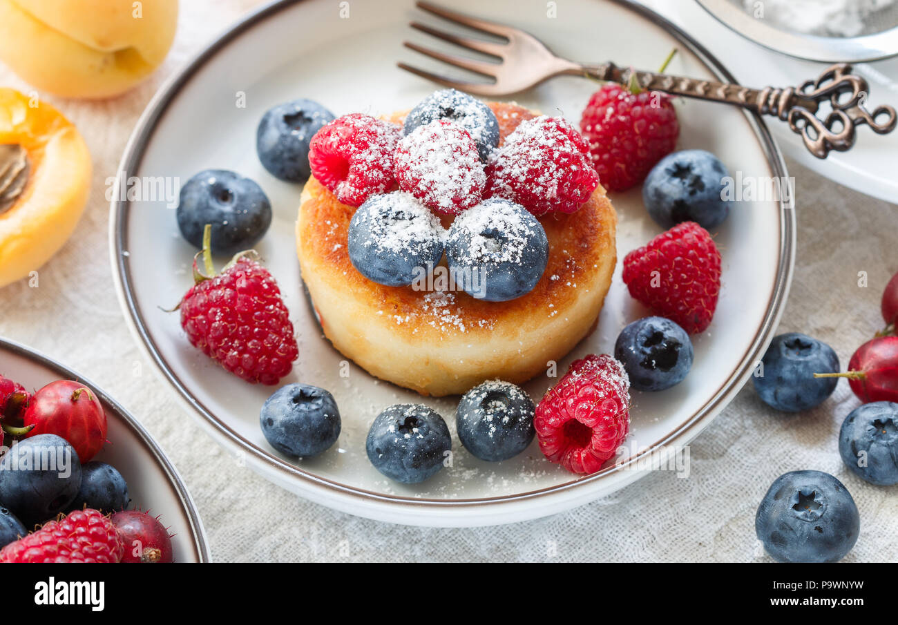 Cottage cheese pancakes, syrniki, curd fritters with fresh berries (raspberry, blueberry, apricot) and powdered sugar in a white plate.  Tasty and hea - Stock Image