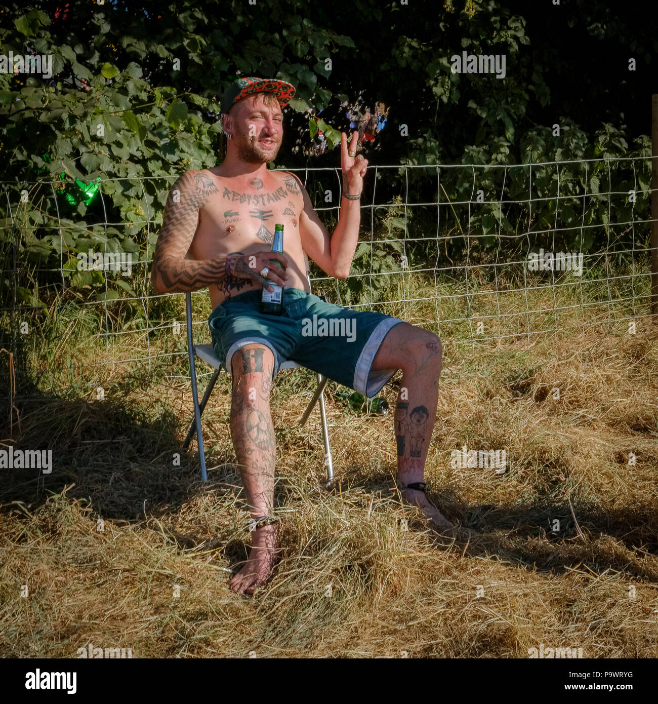 Young man with tattoos and piercings grins and makes the peace sign while drinking from plasticbottle of beer, Latitude Festival, Suffolk, UK. - Stock Image