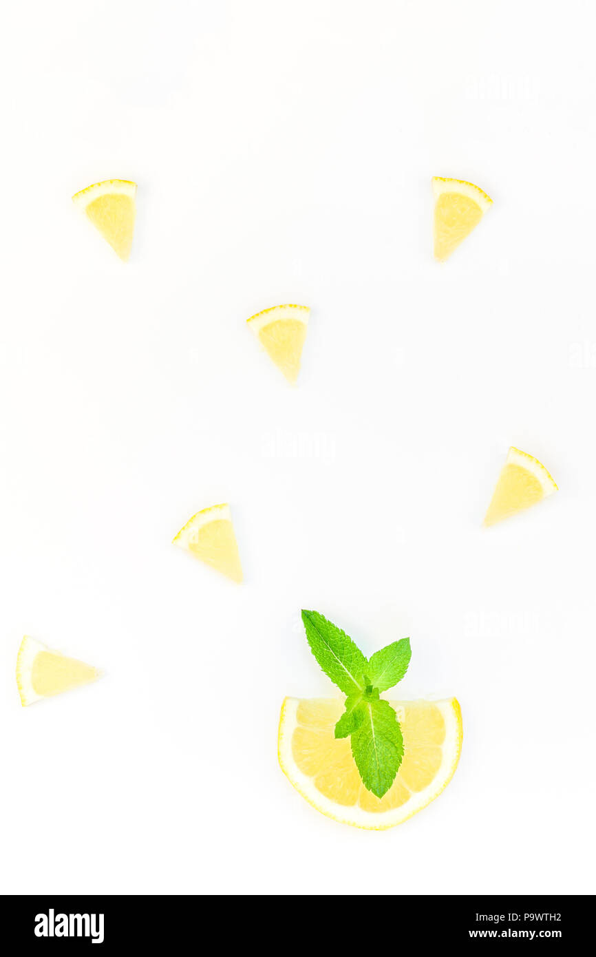 Creative flatlay overhead top view citrus lemon slices and mint herbs leaves white table background with copyspace. Hot summer refreshment lemonade co - Stock Image