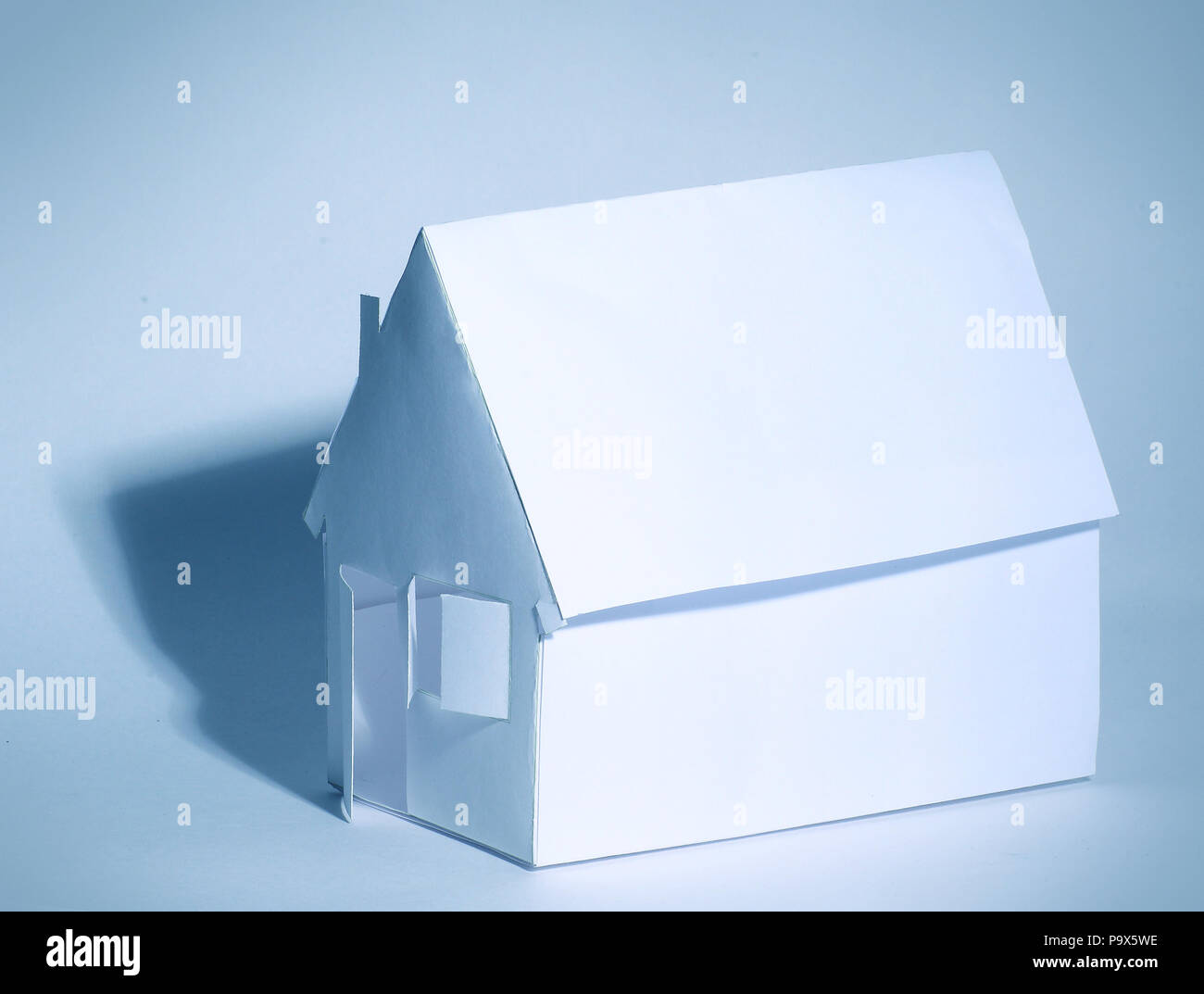 Paper house on a white background in cool colors - Stock Image