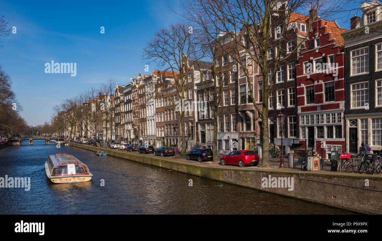 Tall narrow canal houses and a sightseeing tourist cruise boat on a canal in Amsterdam, The Netherlands, Europe - Stock Image
