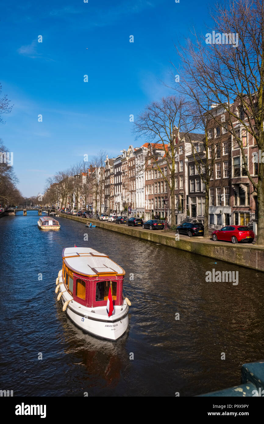 Canal cruises in a pleasure boat with canal houses and tourist cruise boats on a canal in Amsterdam, The Netherlands, Europe - Stock Image