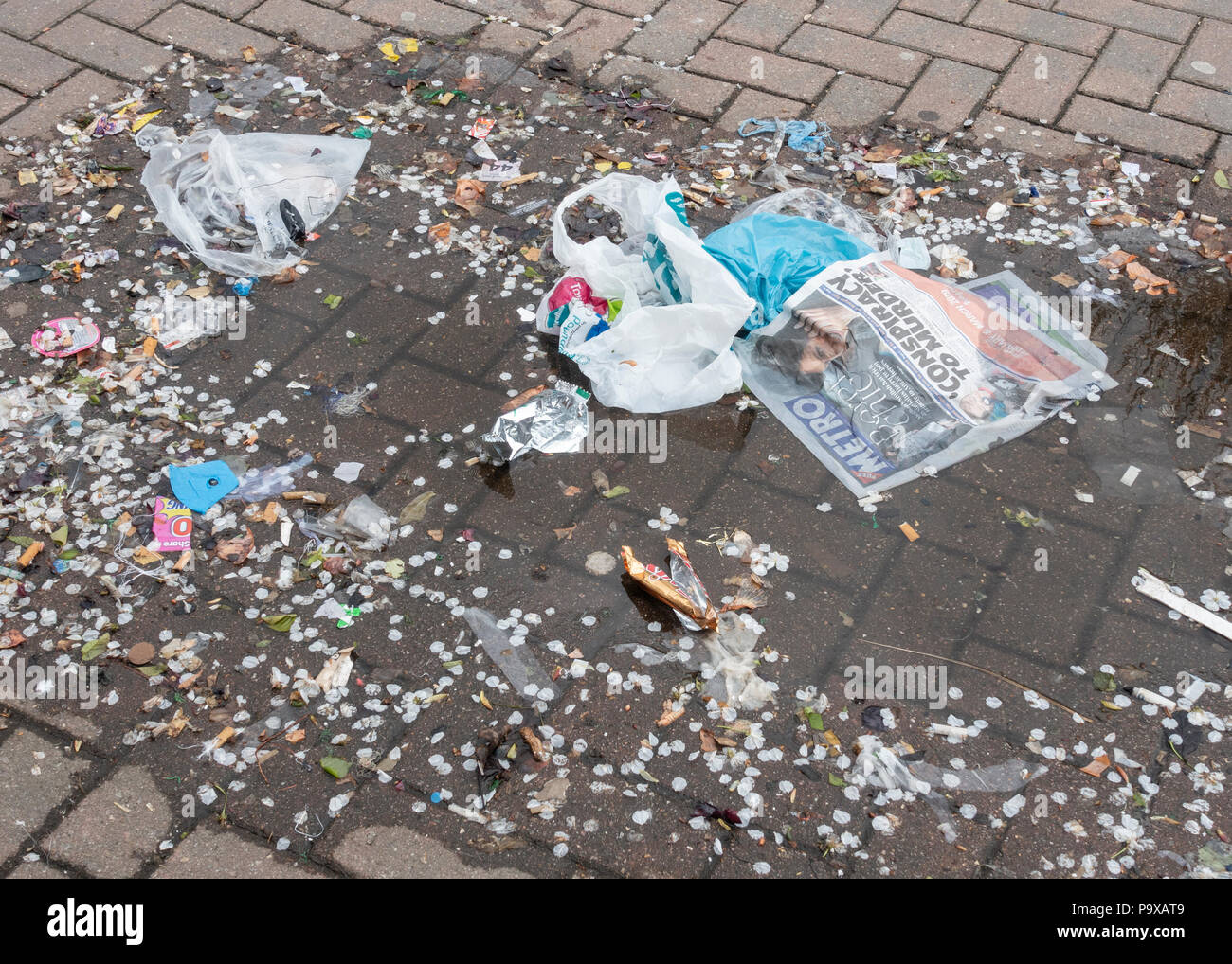 Litter in a puddle on city street in England. UK - Stock Image