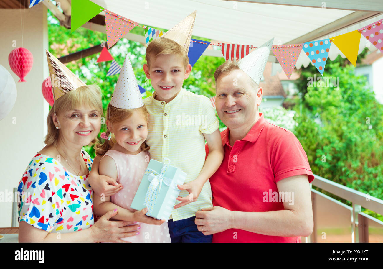 Colorful portrait of happy big family celebrate birthday and grandparents are give gift  their children - Stock Image